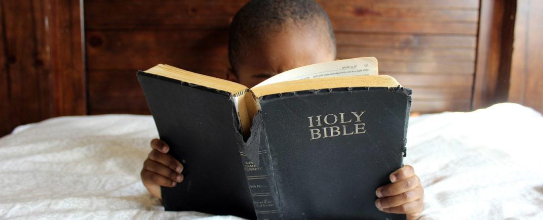 Enfant africain lisant une Bible en anglais