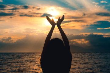 Femme mains levées devant coucher de soleil maritime